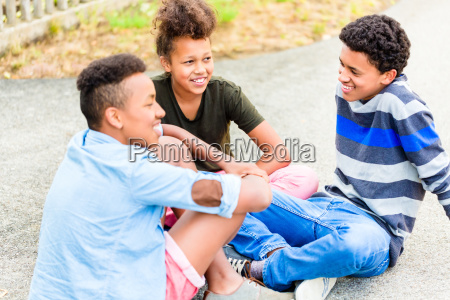 siblings sitting on the ground in
