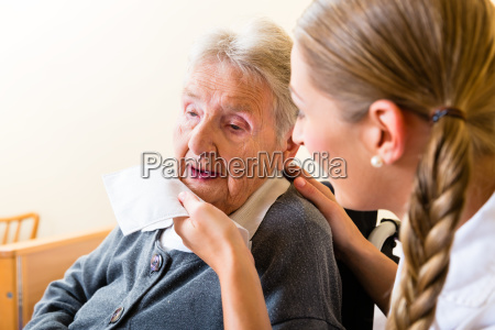 altenpflegerin wipes old womans mouth from