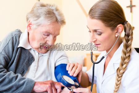 nurse measuring blood pressure in a