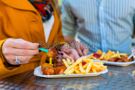 couple eating currywurst at imbissbude