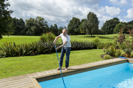 young man cleans a swimming pool