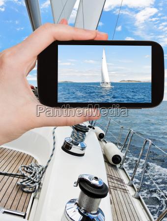 taking photo of white sail yacht