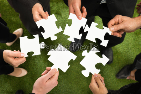 businesspeople, hands, with, jigsaw, puzzle - 13713336