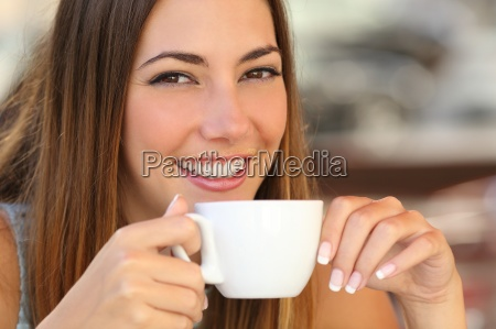 woman tasting a coffee from a
