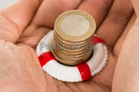 person holding coins and lifebelt