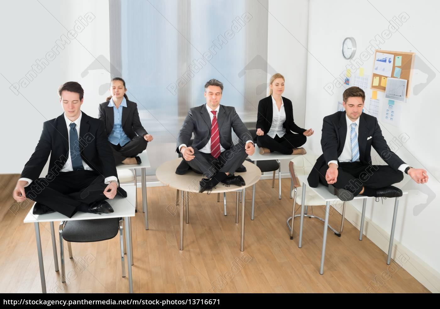 meditating, businesspeople, sitting, on, desk - 13716671