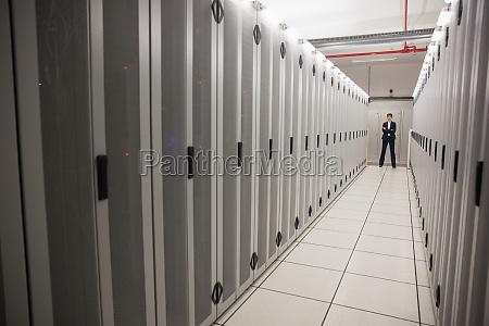 serious technician standing in server hallway