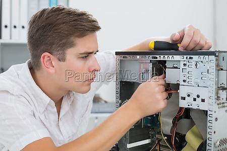 young technician working on broken computer