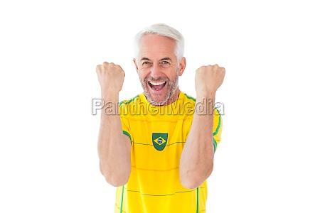cheering brazilian football fan in yellow