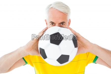 brazilian football fan in yellow holding