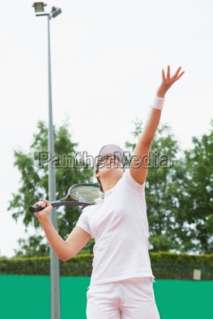 focused tennis player serving the ball