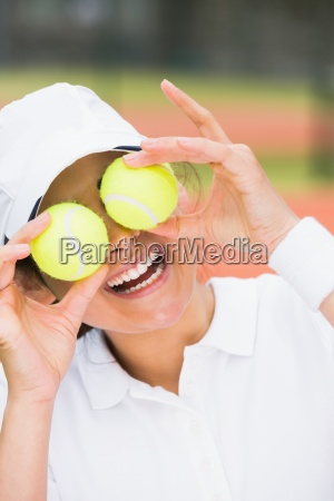 pretty tennis player holding balls over