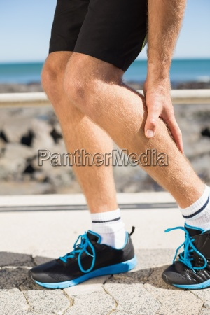 fit man gripping his injured calf
