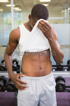 fit man wiping sweat after workout