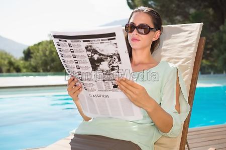 woman reading newspaper on sun lounger