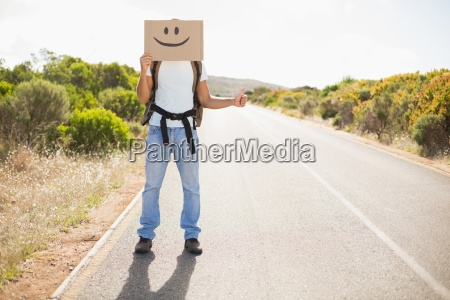 man with smiley face hitchhiking on