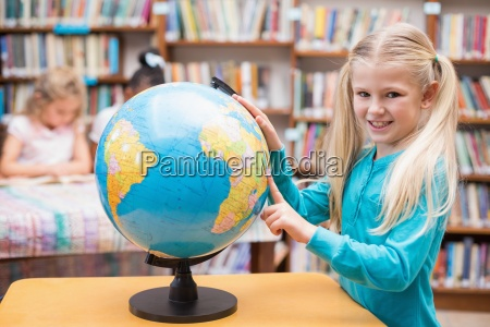 cute pupil looking at globe in