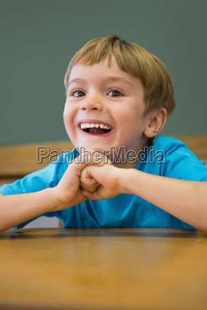 happy pupil sitting at desk in