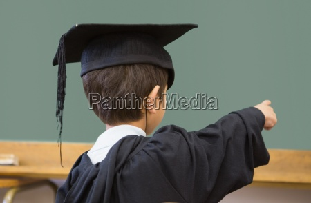 cute pupil in graduation robe pointing