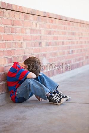 sad, pupil, sitting, alone, in, corridor - 13742321