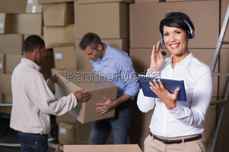 pretty warehouse manager using tablet during