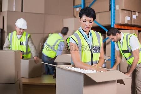 warehouse workers in yellow vests preparing