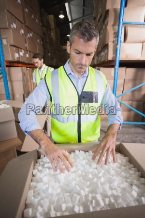 warehouse worker in yellow vest preparing