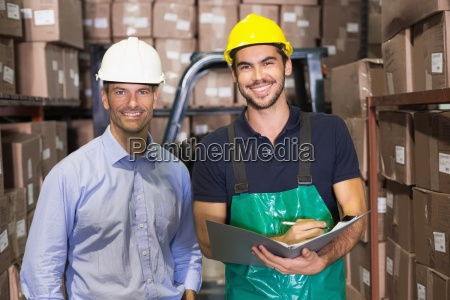 warehouse manager and foreman smiling at