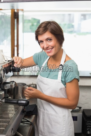 pretty barista steaming jug of milk