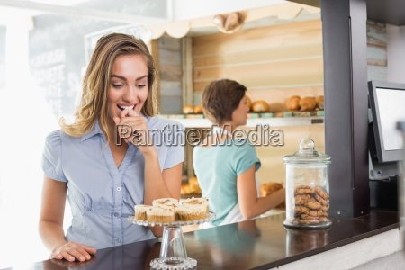 pretty blonde being tempted by cupcakes
