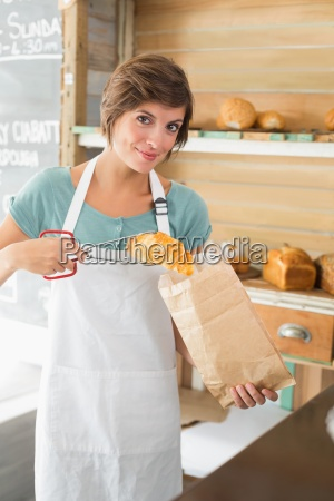 pretty waitress putting croissant in paper