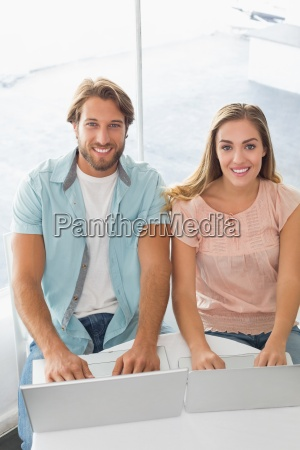 happy couple using their laptops