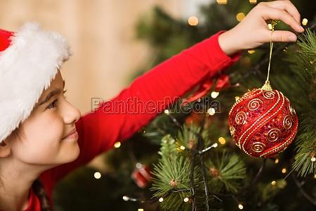 festive little girl hanging a christmas