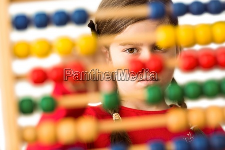 cute little girl using an abacus
