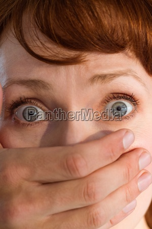 terrified woman with covered mouth