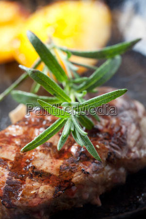 closeup of rosemary on a steak