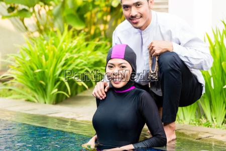 muslim woman in pool greeting her