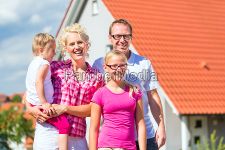 family, stands, proudly, in, front, house - 13774913