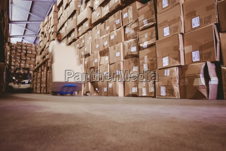 worker with fork pallet truck stacker