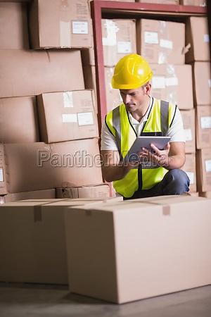 warehouse worker using digital tablet in
