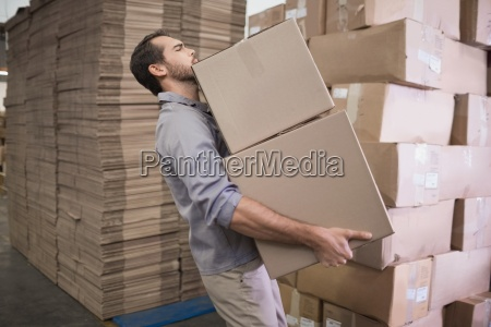 worker carrying boxes in warehouse