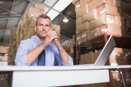 portrait of warehouse manager with laptop