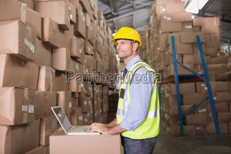 workman with laptop at warehouse