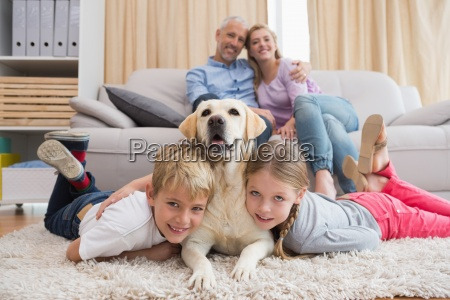 parents watching children on rug with
