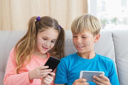 happy siblings using smartphones on sofa