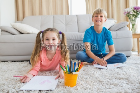 happy siblings colouring on the rug