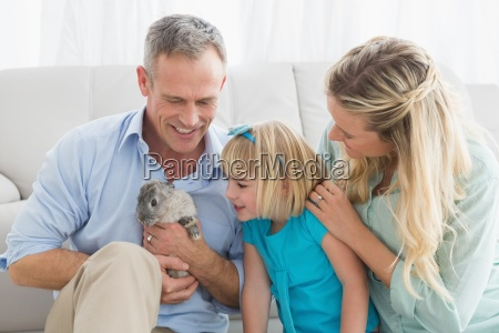 smiling parents and daughter sitting with