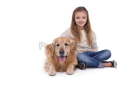 girl sitting beside her pet dog