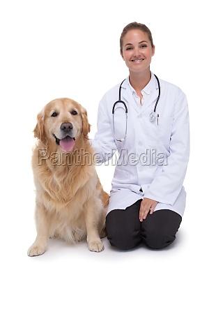 vet kneeling beside a dog