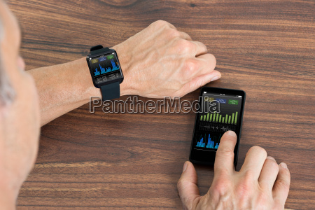 man with smartwatch and cellphone showing